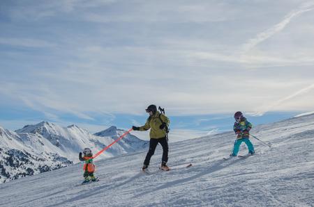 Atemberaubende Aussicht auf die Berge und Skifahrerfamilie im Skigebiet Obertauern