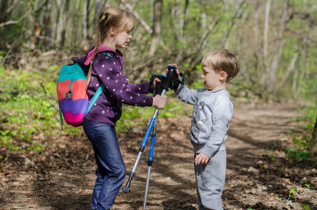 Girl and boy walk or hike through the forest in early spring Reklamní fotografie