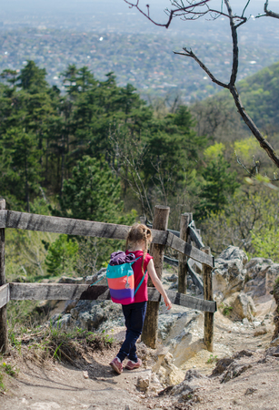 Girl walk or hike through the forest and rocks in early spring