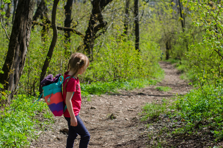 Girl walk or hike through the forest in early spring