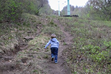 Family walk or hike on trail under chairlift in early spring, April on Buda hills 写真素材
