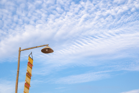 Vintage lamp on top of bamboo pole and yellow lanna flag(Tung) on the blue sky in the morning.