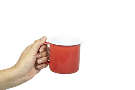 Female hands holding red tin cup on white background.