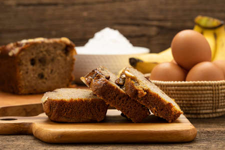 Banana bread on wooden plate with banana on wooden table and yellow background.