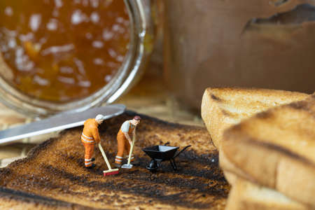 Miniature people are cleaning out burnt toast.