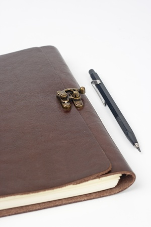 Leather notepad with drawing pencil on white background photo