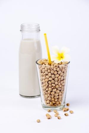 soya: leche de soya fresca y soja crudo sobre fondo blanco