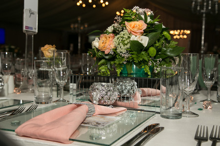 Décorations de mariage avec des verres, des couverts et des roses et serviette