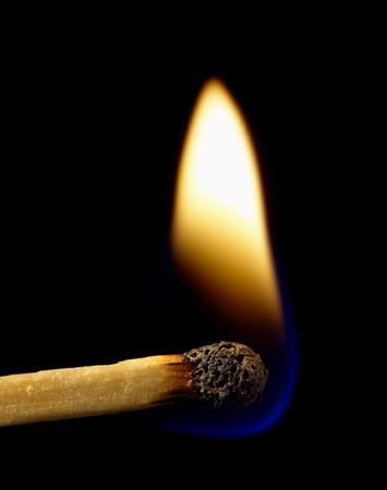 Burning match on a black background photo