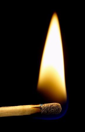 Burning matchstick on black background, isolated over black photo