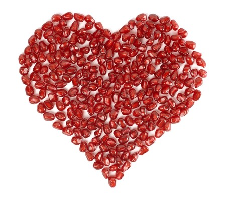 Valentines heart made of pomegranate seeds, isolated over white