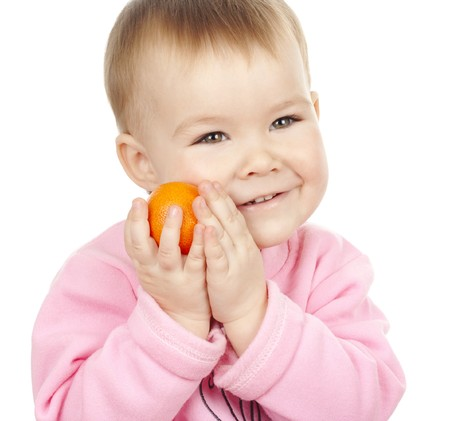 clasping: Adorable child holds mandarin clasping it to his cheek, isolated over white