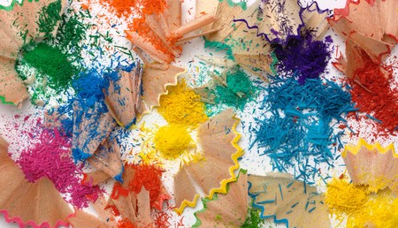 Bright multi-colored crayons shavings on white paper photo