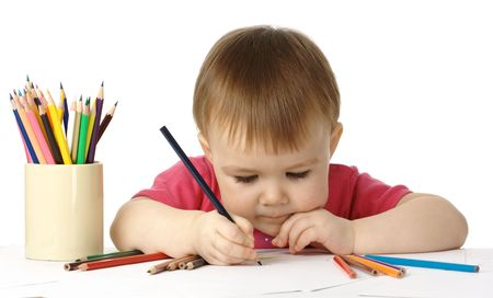 focusing: Cute child, focused, drawing on white paper, isolated