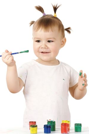Little girl holds paintbrush filled with green paint, isolated over white photo