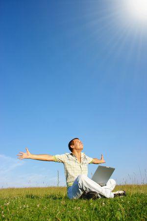 educacion gratis: Feliz estudiante con ordenador port�til en verde prado, d�a soleado Foto de archivo