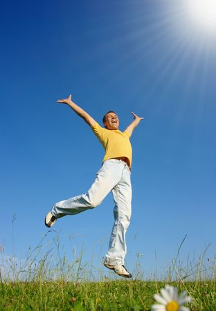 Happy young man jumping on the meadow, summer sunny day photo