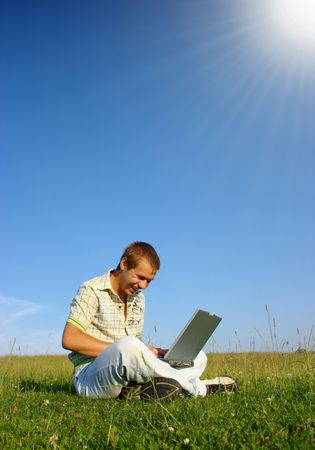 Happy student working with laptop on green meadow, summer sunny day photo