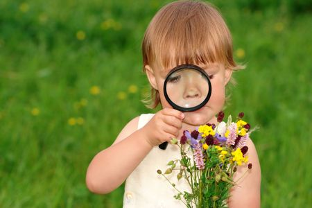 Cute little girl looking at bouquet of field flowers through magnifying glass photo