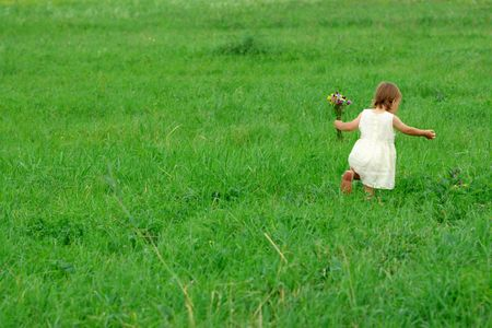 Little girl walking on green meadow with bouquet of field flowers photo