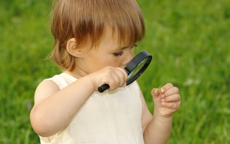Cute child looking at little snail through magnifying glass photo