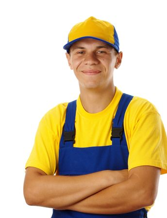 journeyman: Happy young worker fold his arms, dressed in blue-and-yellow uniform and baseball hat, isolated over white