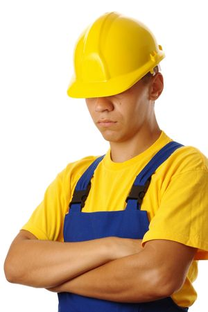 journeyman: Serious young worker pull hardhat over his eyes, wearing blue-and-yellow uniform, isolated on white