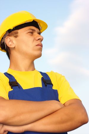 Portrait of a young construction worker, dressed in blue-and-yellow uniform and hard hat, over blue sky photo