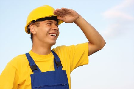 Young cheerful worker looking forward, covering eyes from the sun, dressed in blue-and-yellow uniform and hard hat, over blue sky photo