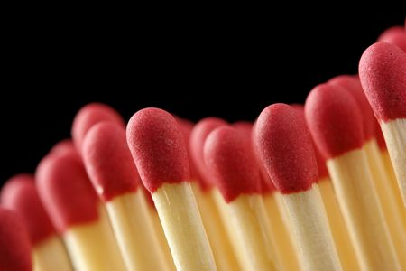 conscription: Wave of red matchsticks, shallow DOF, isolated on black background