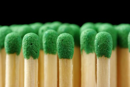 conscription: Line of green matchsticks, shallow DOF, isolated on black background