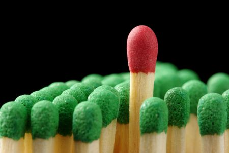 matchstick: Single red matchstick among green ones, out of the crowd concept, isolated over black