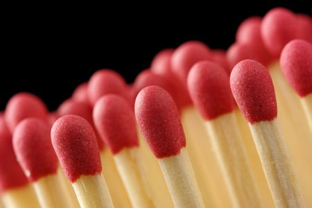conscription: Line of red matchsticks, shallow DOF, isolated on black background