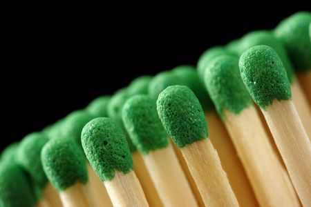 Line of green matchsticks, shallow DOF, isolated on black background photo