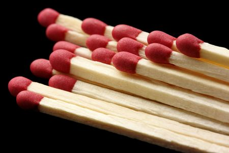 conscription: Few red matchsticks, shallow DOF, isolated on black background