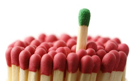 Single green matchstick among red ones, out of the crowd concept, isolated over black