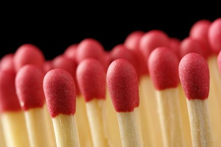 Line of red matchsticks, shallow DOF, isolated on black background photo