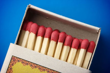Red matchsticks in the box on blue background, shallow DOF photo