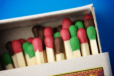 Multicolored matchsticks in the box on blue background, shallow DOF photo