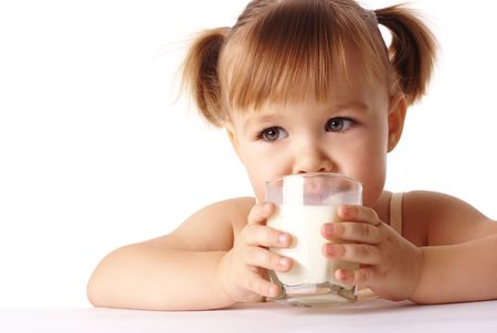 glass of milk: Cute little girl drinks milk, isolated over white