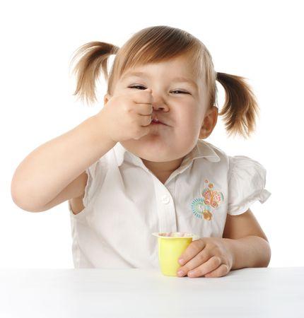 Cute little girl eats yogurt , isolated over white Stock Photo - 6085540