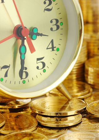 Old-fashioned clock dial on golden coins background, time is money concept photo