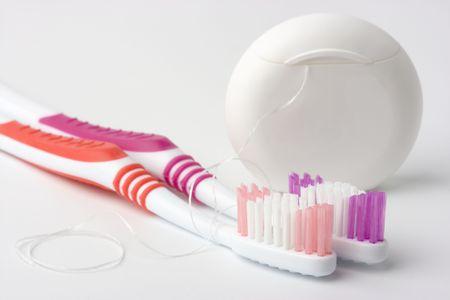 artigos de higiene pessoal: Two toothbrushes and dental floss - common toiletries Imagens