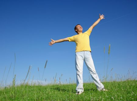 Happy young man in casual on the meadow, smile spreading his arms, summer sunny day photo