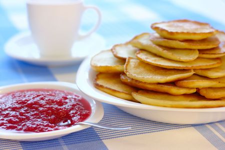 Fresh small pancakes with raspberry jam - traditional Russian cuisine photo