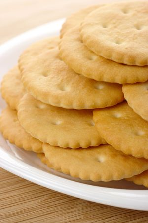 Fresh yellow round crackers on white plate Stock Photo - 6247642