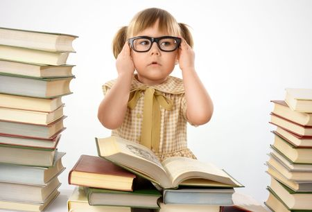 Little girl surrounded by books wearing black glasses, back to school concept, isolated over white photo