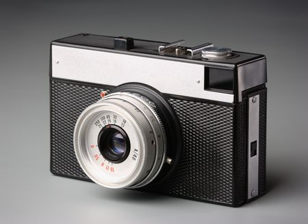 White metal and black plastic old-fashioned camera, isolated over white photo