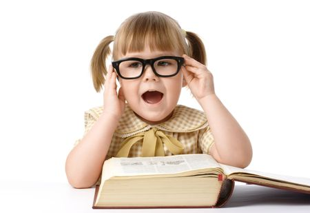 Happy little girl with big book wearing black glasses, isolated over white photo