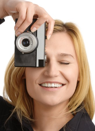 young attractive woman taking a shot with retro photo camera, isolated over white photo